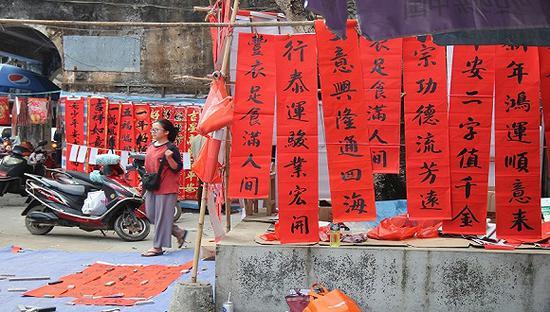帮家人照看对联摊子的小镇青年。摄影:邓雅蔓