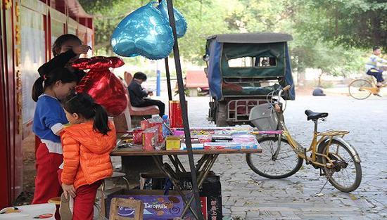腊月二十八,在整理鞭炮摊子的三位小镇姑娘 摄影:邓雅蔓
