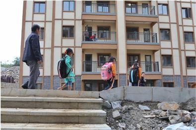 易地扶贫搬迁至县城后,教师杨绍书和学生从新居内走出前往新学校(5月7日摄)。