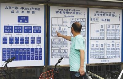 6月6日,考生家长在101中学校外观看考场分布图。
