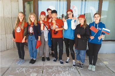 俄罗斯孩子们与自己作品合影时,笑得十分开心。