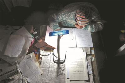邹伟敏在家中挑灯夜读。