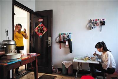 5月31日,出租房内,女儿在吃饭,杨雨菲在一旁忙家务。