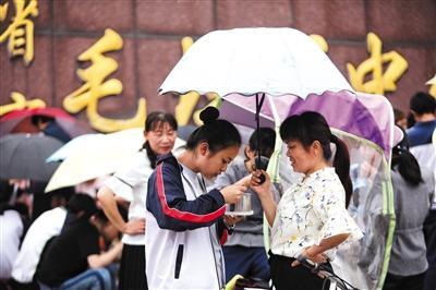 5月30日,毛坦厂中学东门外,陪读家长为站着就餐的孩子撑伞。