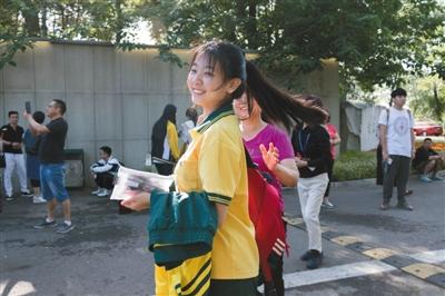 6月7日上午,北京市101中学考点,考生与母亲击掌后笑着进考场。新京报实习生 陈婉婷 摄
