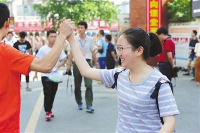 7日,在安徽省阜阳市第十五中学考点,一名考生进考场时与送考老师击掌加油。   王 彪摄(人民视觉)