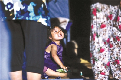 6月20日晚,小女孩在家人旁边开心地玩耍