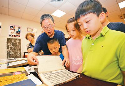 学生们在老师指导下参观复旦大学中华古籍保护研究院收藏的古籍珍品。陆嘉辉摄