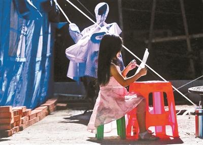 6月20日,小女孩在凳子上写语文作业