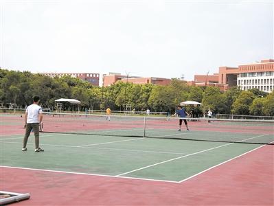 学生在网球场打网球。