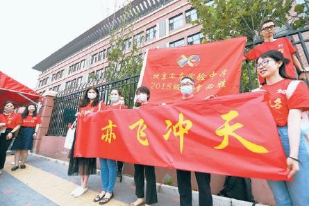 今天,北京人大附中經開學??键c,幾名老師統一身穿紅色T恤,打出橫幅為學生加油鼓勁。 本報記者 和冠欣 攝
