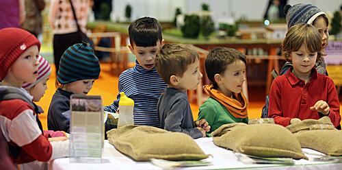 资料图片:孩子们在德国农产品展销会上学习辨认农作物。(新华社)