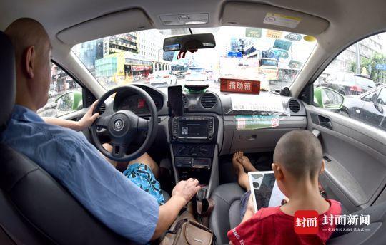 8月7日,成都红星路,小伟在冯军的车里看动画片。