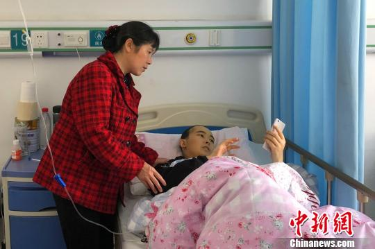 杨晓龙浏览朋友发来鼓励他的信息 袁雪梅 摄