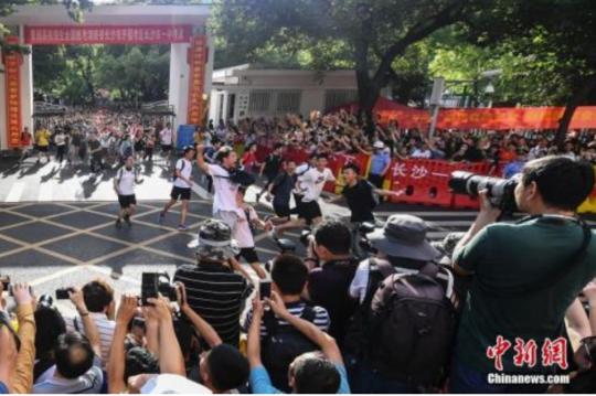 资料图:6月8日下午,湖南长沙市一中考点外,考生跑出考场,庆祝高考结束。 中新社记者 杨华峰 摄