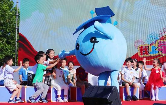"""小学生们开心的与""""蓝博豆""""击掌"""