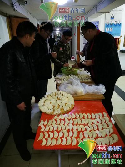 图为学生与宿管叔叔阿姨在楼道间包饺子。中国青年网通讯员 李蕙君 摄