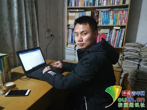 图为闫春旭坐在电脑前修改文章。受访者供图