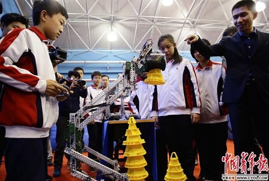 北京一七一中学机器人社团的李政坤(左)同学正在演示智能机械臂的使用