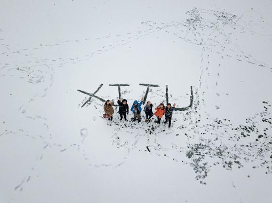 """1月3日,西安交通大学学生在雪地里""""绘出""""校名英文缩写""""XJTU""""字样,李斌摄。"""
