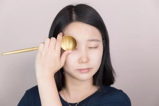 然后再依次用手指将睫毛贴近勺子,顺着勺子的弧度轻轻拈起睫毛。