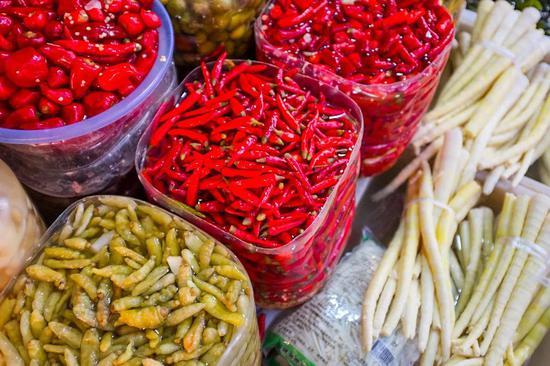在汇川区的各大菜市场中,不同种类的酸味腌制品极为常见。光是酸制的辣椒便有糟辣椒、泡椒等多种。摄影/韩诗扬