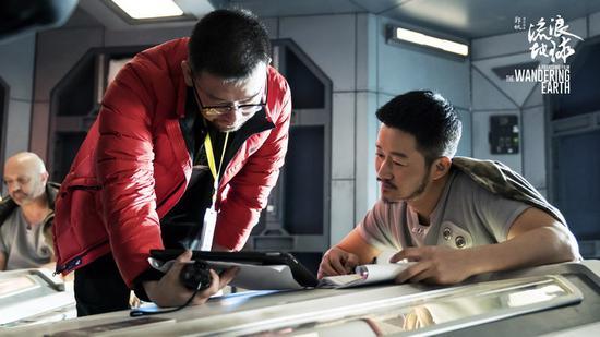 吴京与导演郭帆(左)交流。