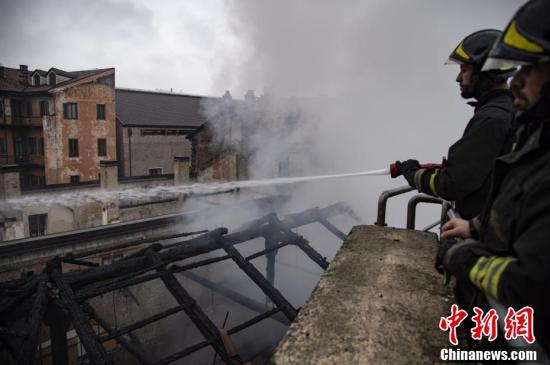 图为消防员使用喷水枪在火场灭火