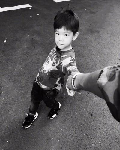 照片中嗯哼牵着爸爸的手仰视镜头吐舌卖萌,这帅气的小脸蛋萌炸了