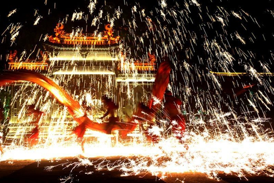 Performers spray molten iron to entertain visitors during May Day holiday in Shandong
