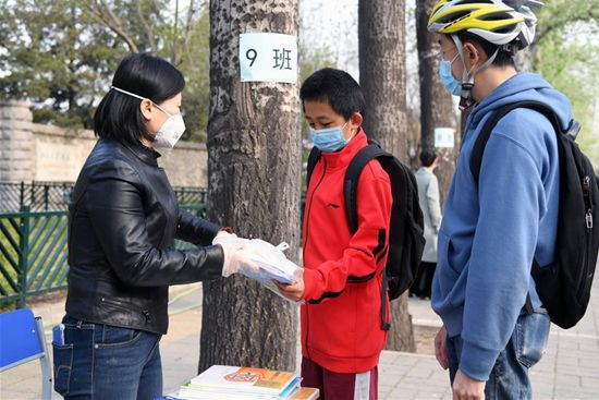 Beijing's primary school distributes textbooks for online teaching to students