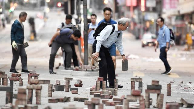 Hong Kong residents say 'no' to violence by clearing barricades, mourning innocent victim
