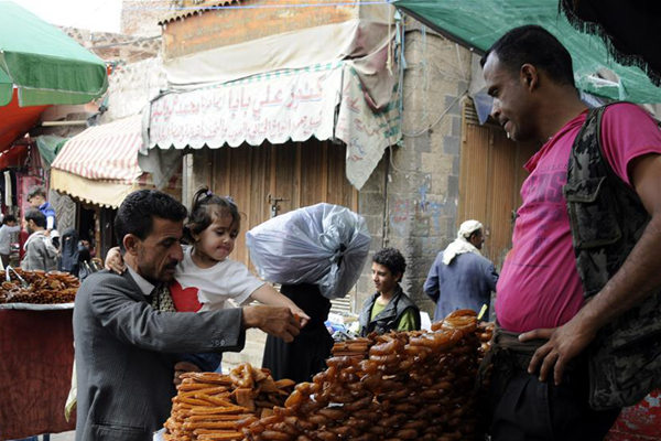 A man purchases sweets for breakfast at a market during the Islamic holy month of Ramadan in Sanaa, Yemen, June 8, 2017. (Xinhua/Mohammed Mohammed)