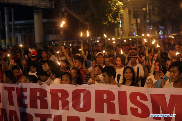 Activists hold placards during a protest rally in Manila, the Philippines, June 12, 2017. The protesters called for the end of terrorism in the country and the lifting of President Rodrigo Duterte's declaration of martial law in Mindanao. (Xinhua/ROUELLE UMALI)