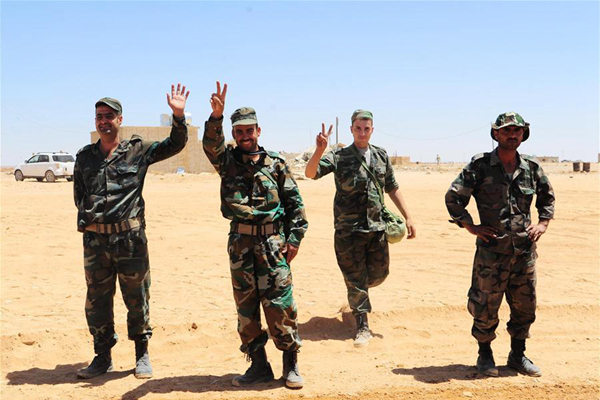 Syrian soldiers gesture in the Syrian desert at the countryside of the central Homs province near the Syrian-Iraqi borders, on June 12, 2017. The Syrian army recently announced that the Syrian forces and allied troops have completed the first stage of the military operation in the Syrian Desert, by reaching the Syrian-Iraqi borders after battles with the Islamic State (IS) group. (Xinhua/Ammar Safarjalani)