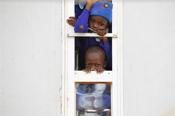 Pupils watch the donation ceremony at Beijing MCEDO School in Nairobi, Kenya, June 15, 2017. Dozens of Chinese firms on Thursday donated learning materials, sports kits and snacks worth 4,075 U.S. dollars to a school located in the Mathare slum in Kenya's Nairobi. (Xinhua/Chen Cheng)
