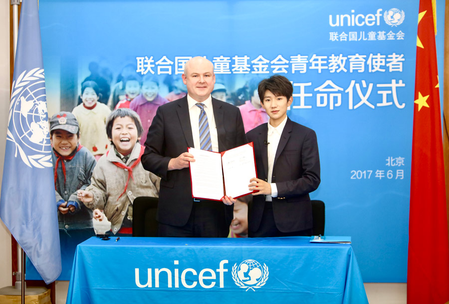 UNICEF China Acting Representative Dr. Douglas Noble and well known Chinese singer and actor, a member of the pop band TFBOYS, Wang Yuan, showcase a UNICEF Special Advocate for Education appointment letter at an event at UNICEF's Beijing office on 28 June, 2017. Photo:UNICEF/China/2017/Xia Yong
