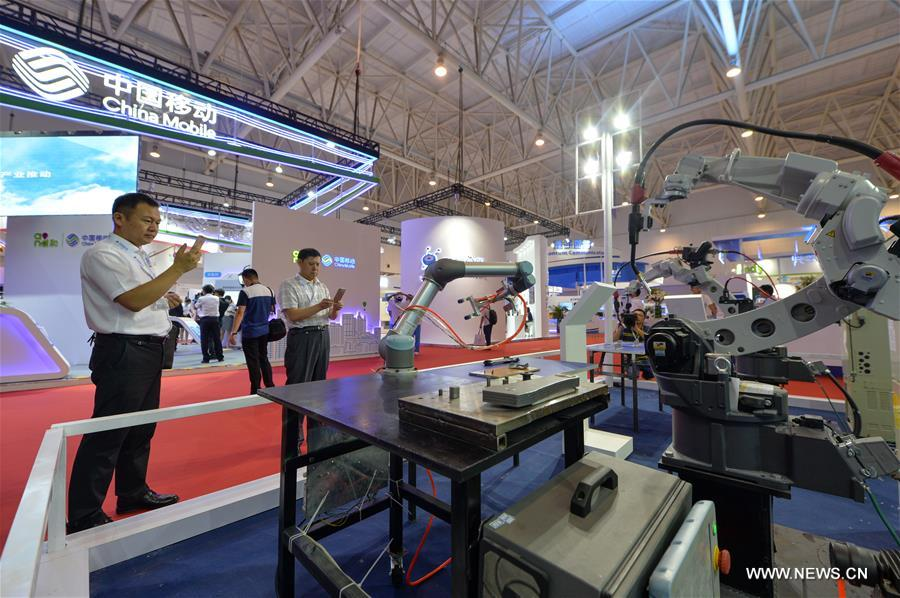 Visitors take photos of intelligent products displayed during the first World Intelligence Congress in Tianjin, north China, June 29, 2017. The congress opened here on Thursday. (Xinhua/Bai Yu)