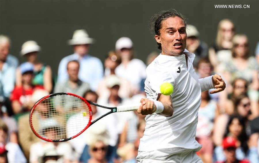 Ukraine's Alexandr Dolgopolov hits a return during the men's singles first round match against Switzerland's Roger Federer at the Championship Wimbledon 2017 in London, Britain, on July 4, 2017. Federer advanced to the second round after Dolgopolov retired due to injury. (Xinhua/Tang Shi)
