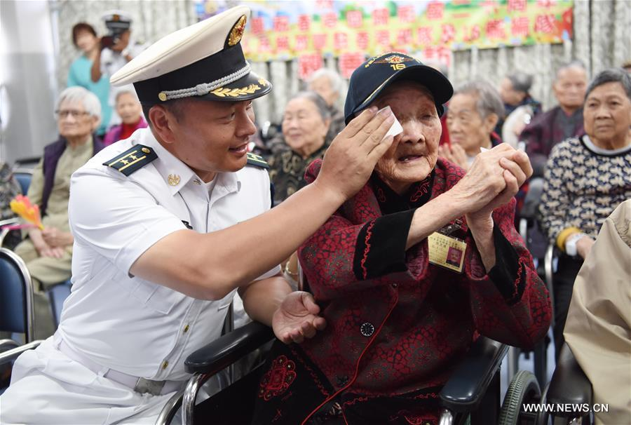 An officer of China's aircraft carrier Liaoning wipes tears for a 110-year-old woman during their visit to the Ho Leung Kit Ting Care and Attention Home of Asia Women's League Limited in Hong Kong, south China, July 10, 2017. About 60 soldiers and officers of aircraft carrier Liaoning visited the elders of the care and attention home on Monday. (Xinhua/Wang Shen)