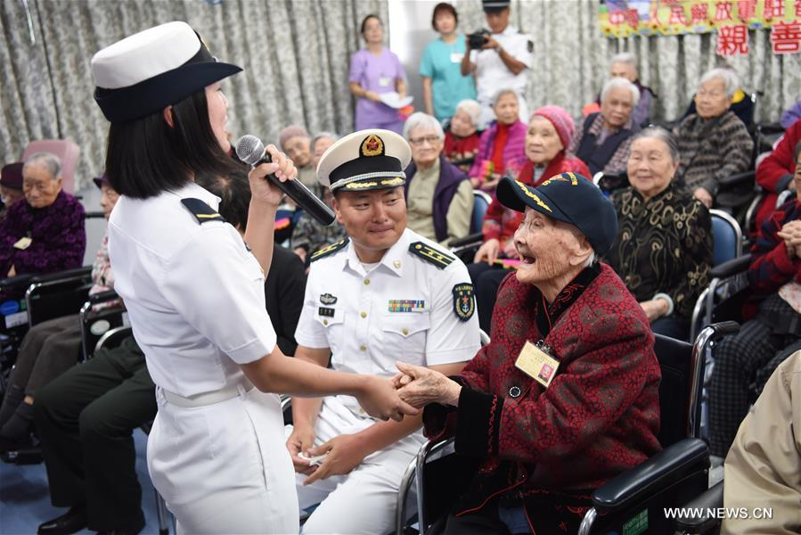 A soldier of China's aircraft carrier Liaoning sings songs when visiting the Ho Leung Kit Ting Care and Attention Home of Asia Women's League Limited in Hong Kong, south China, July 10, 2017. About 60 soldiers and officers of aircraft carrier Liaoning visited the elders of the care and attention home on Monday. (Xinhua/Wang Shen)