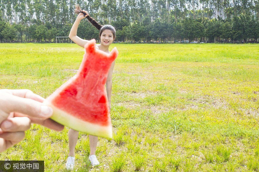 A woman poses with a piece of watermelon shaped like a dress at Guangzhou University Town, South China's Guangdong province, July 7, 2017. [Photo/VCG]