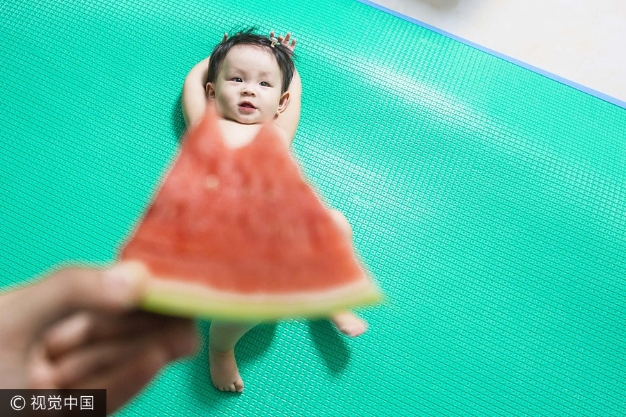 A baby poses with watermelon shaped like a dress at Guangzhou University Town in South China's Guangdong province, July 7, 2017. [Photo/VCG]
