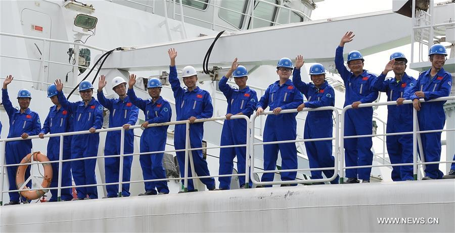 Expedition team members wave goodbye aboard the comprehensive research vessel, the Kexue (Science), in Qingdao, east China's Shandong Province, July 10, 2017. The 99.6-meter-long and 17.8-meter-wide ship carrying scientific detection equipments domestically developed by China set off here Monday. (Xinhua/Zhang Xudong)