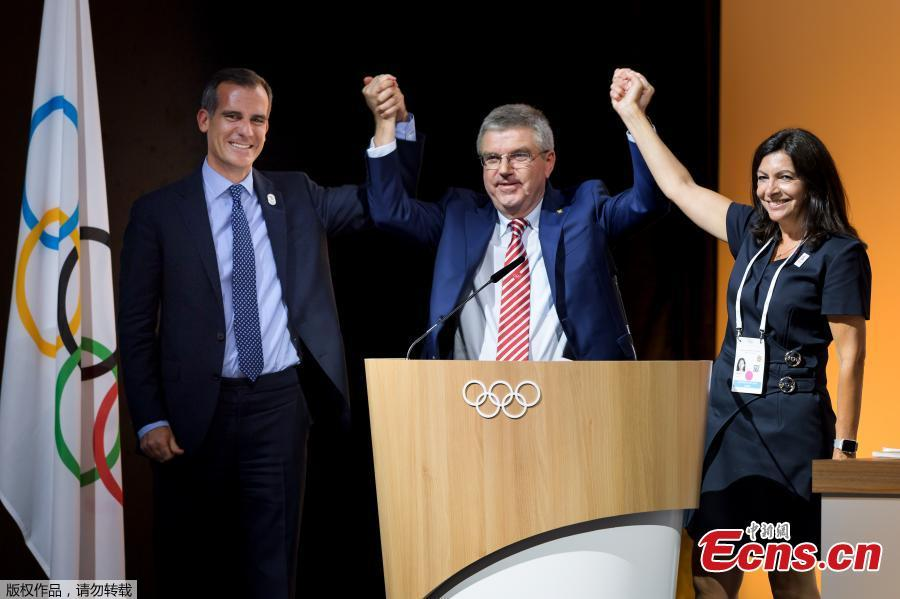 (LtoR) Mayor of Paris Anne Hidalgo, International Olympic Committee (IOC) President German Thomas Bach and Los Angeles Mayor Eric Garcetti reacts on the podium during an International Olympic Committee (IOC) extraordinary session on July 11, 2017 in Lausanne. The International Olympic Committee on July 11 agreed to award the 2024 and 2028 Games at the same time, effectively guaranteeing that Paris and Los Angeles will be the hosts. (Photo/Agencies)