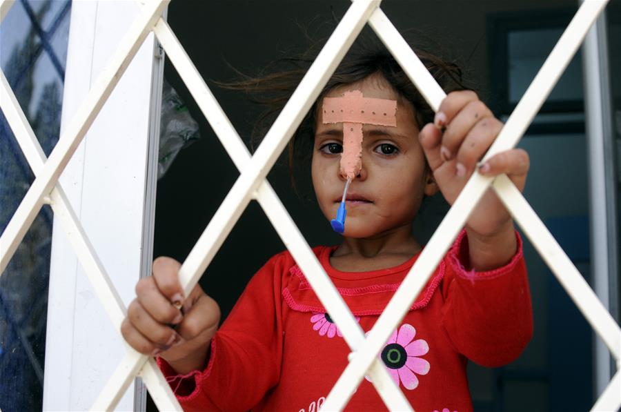 A cholera-infected girl looks out of a window as she receives medical treatment at a hospital in Sanaa, Yemen, on July 11, 2017. Cholera disease has infected more than 300,000 people in war-torn Yemen since late April, the international Committee of the Red Cross (ICRC) said on Monday. (Xinhua/Mohammed Mohammed)