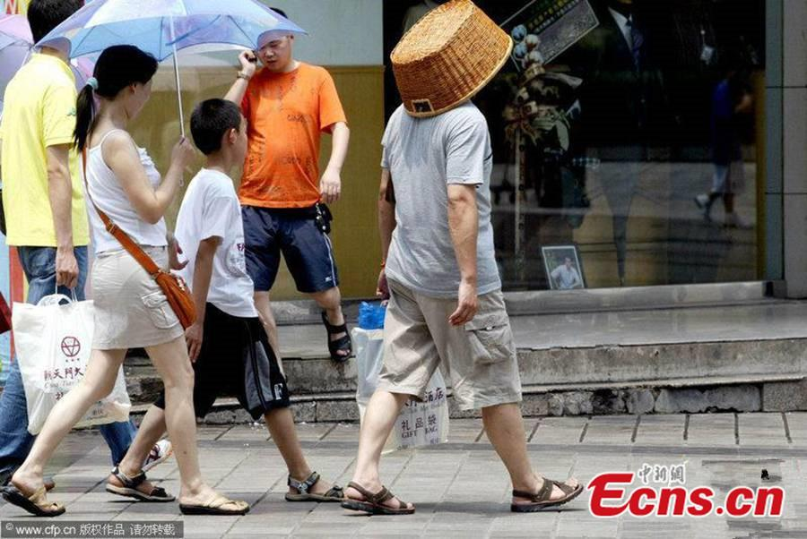 A man uses a grocery basket over his head to keep the sun off as temperature reaches 40 C in Chongqing, July 15, 2006.(Photo/VCG)