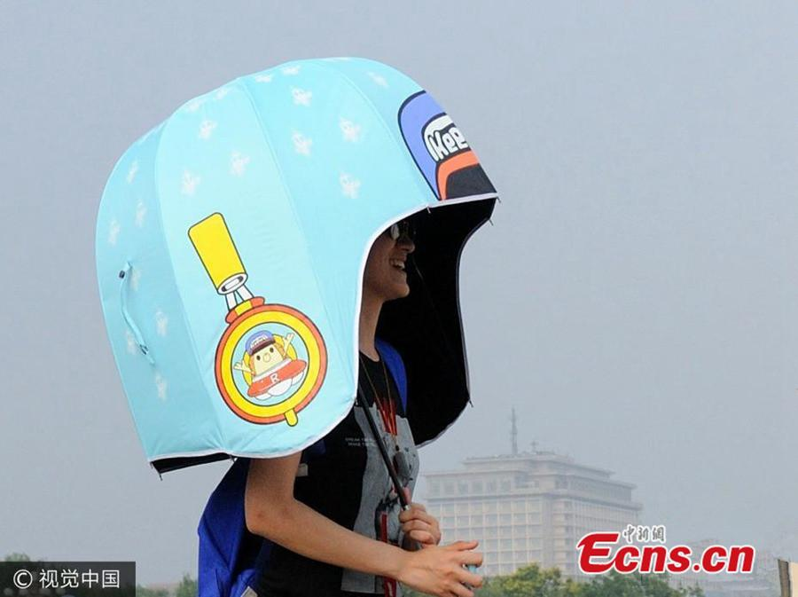 A woman holds an umbrella in the shape of a giant bike helmet to keep out of the baking sun in Chang'an avenue, Beijing, Aug 6, 2016.(Photo/VCG)