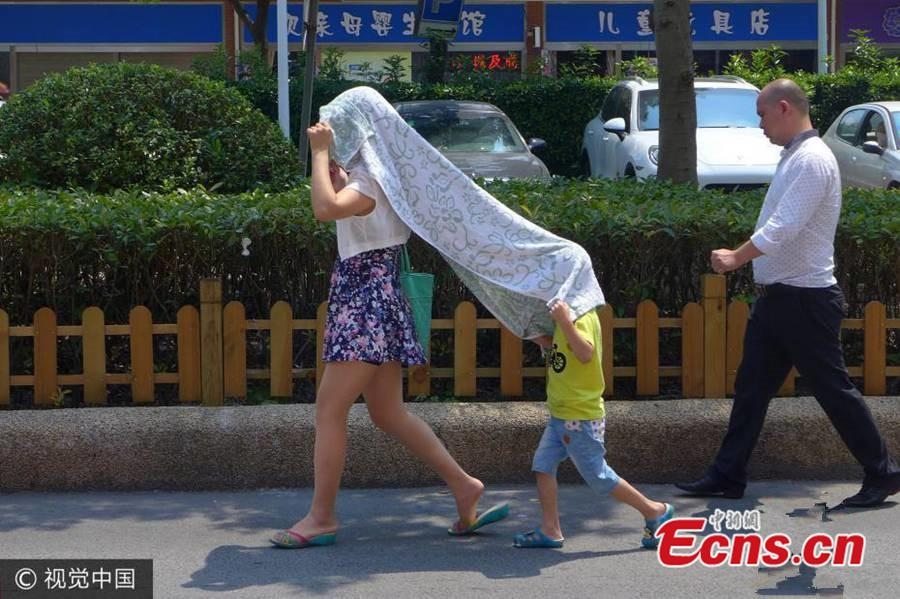 A mother and her son take cover from the sun's rays under a towel in Shanghai, Aug 2, 2015.(Photo/VCG)