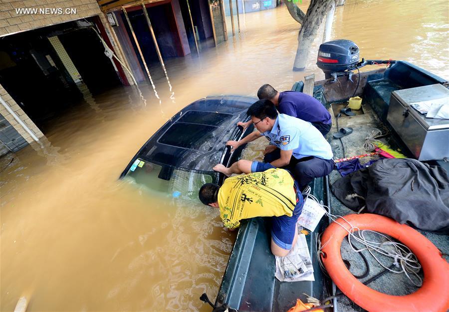Policeman Zeng Kai (C) and his colleagues fix a car submerged in water in Liuzhou City, south China's Guangxi Zhuang Autonomous Region, July 12, 2017. The Liuzhou section of Liujiang River's water level reached 83.63 meters Wednesday, 1.13 meters higher than the warning line. (Xinhua/Li Hanchi)